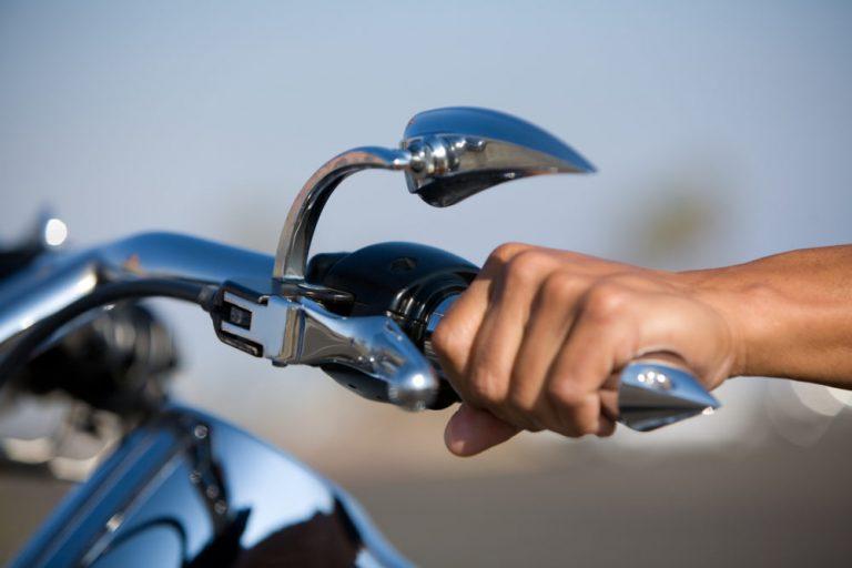 Homem segurando em guidão metálico de uma moto