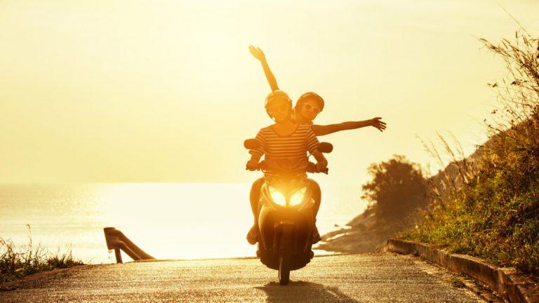Casal andando de moto sem estresse em nascer do sol