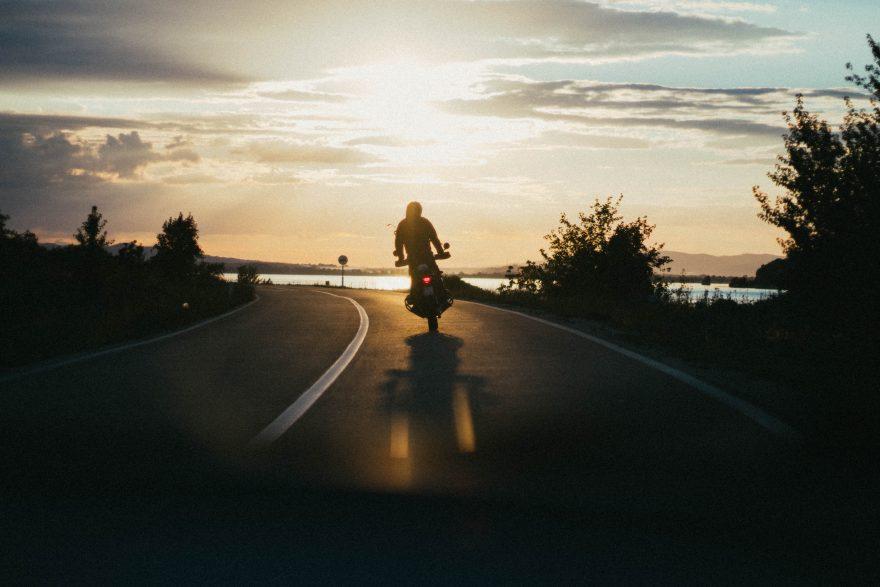 Pessoa andando de moto em uma estrada no fim de tarde